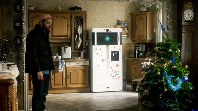 Jérem steht in seiner Küche mit dem Kühlschrank