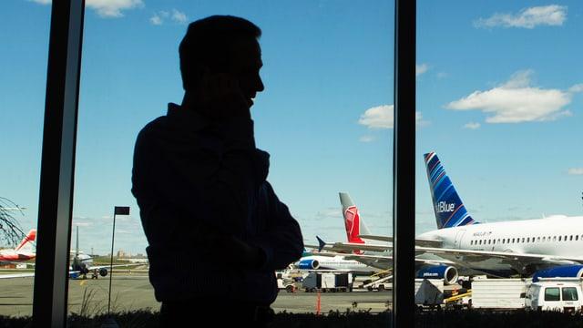 Person im Gegenlicht telefoniert vor einem Fenster auf einem Flughafen, im Hintergrund Flugzeuge