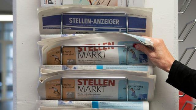 Eine Person nimmt einen Stellenanzeiger aus einem Zeitungshalter, aufgenommen am 11. November 2014 im Regionalen Arbeitsvermittlungszentrums RAV in Bern.