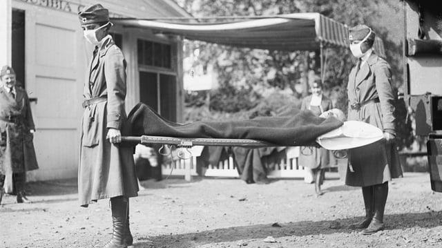 Zwei Frauen tragen eine Bahre mit einem Kranken darauf zwischen sich