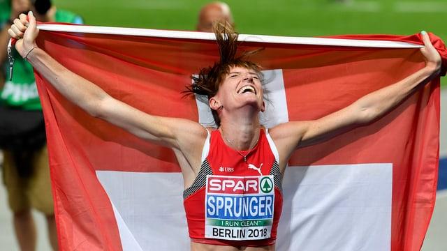 Purtret da Lea Sprunger che tegna ina bandiera svizra enta maun.