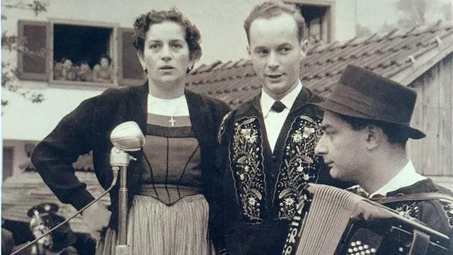 Schwarz-Weiss-Fotografie von einem singenden Paar, das von einem Akkordeonisten begleitet wird.