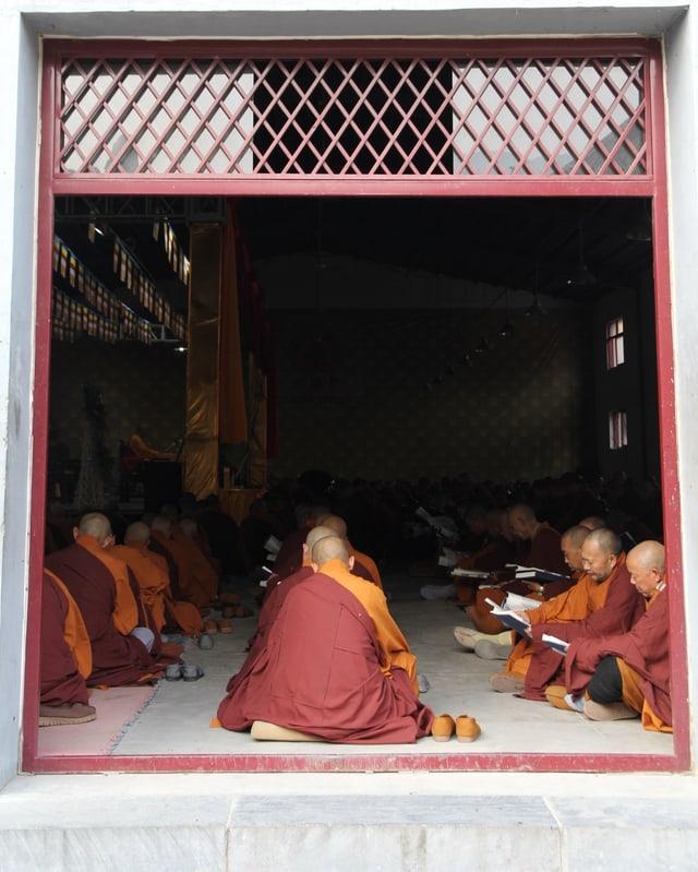Mönche sitzen in einem Raum uns lesen.