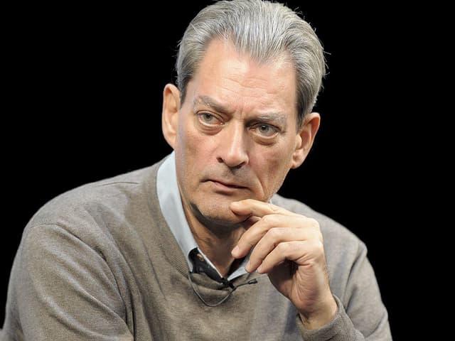 Der Autor Paul Auster mit grauem Pullover und der Hand an seinem Kinn.