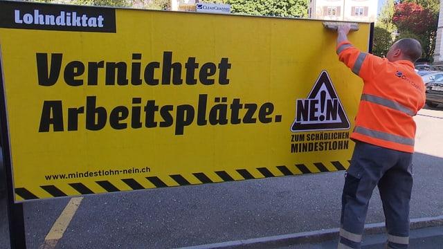 """Ein Mann hängt ein Plakat der Gegner der Mindestlohninitiative auf. Auf dem Plakat steht der Slogan: """"Vernichtet Arbeitsplätze""""."""