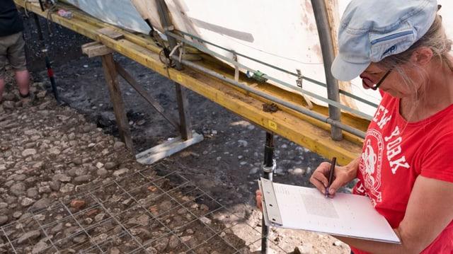 Eine Grabungssättte: Eine Frau schreibt in einen Block Beobachtungen im Hintergrund Schotter