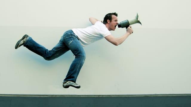 Ein Mann schreit in ein Megaphon. Er scheint über dem Boden zu schweben.