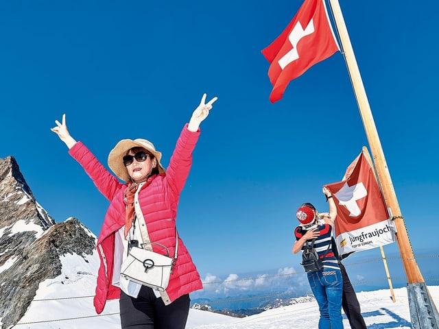 """EIne Frau mit Sonnenbrille mit ausgestreckten Händen und """"Victory""""-Zeichen vor einer Schweizerfahne"""