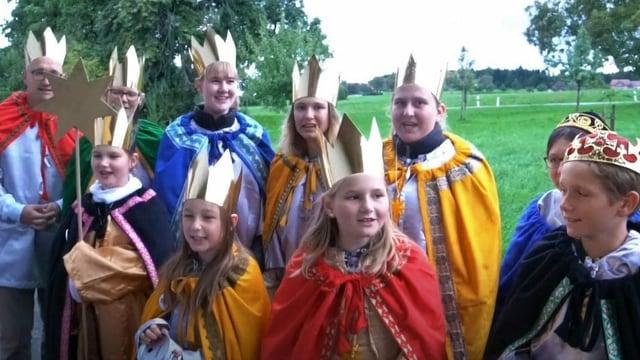 Eine Gruppe von Menschen mit Kindern mit goldiger Krone und Gewand am singen