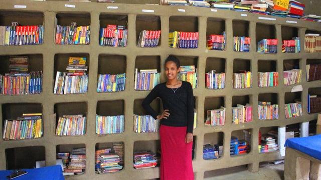 Eine Frau steht vor einer Bücherwand