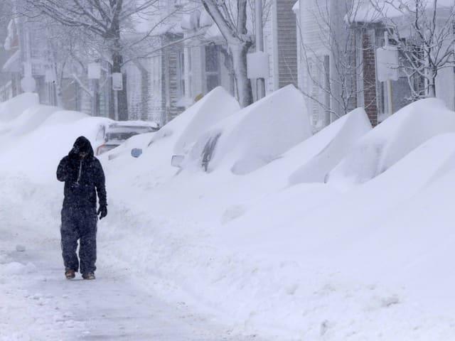Mann läuft an verschneiten Autos vorbei