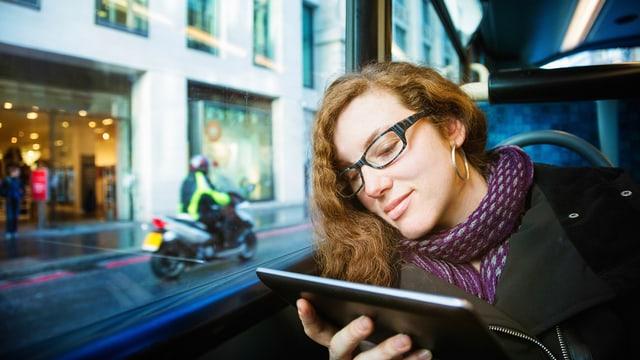 Junge Frau mit Tabletcomputer in Strassenbahn