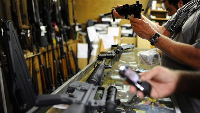 Männer in Waffengeschäft stehend, Waffen begutachtend