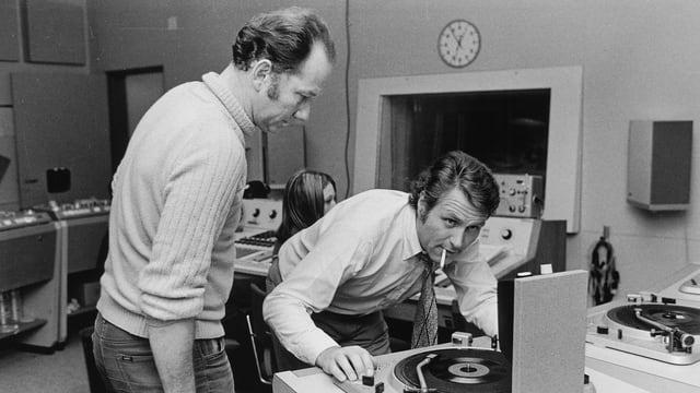 «Nachtexpress»-Moderator Ueli Beck und Techniker Gustav Hofstetter beim Auflegen einer Schallplatte. Aufgenommen 1970 im Studio Zürich.