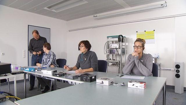 Drei Personen am Tisch prüfen die Klangqualität der Ohrhörer.