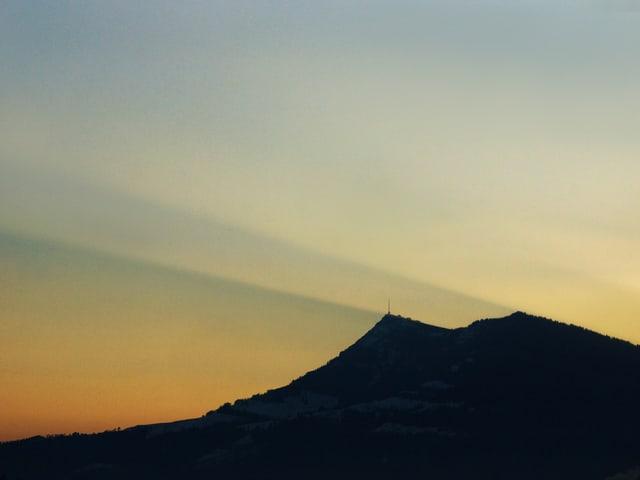 Die Sonnenstrahlen sind im sanften Morgenlicht gut Sichtbar. Unten die dunkle Silhouette der Rigi, darüber blauer Himmel.