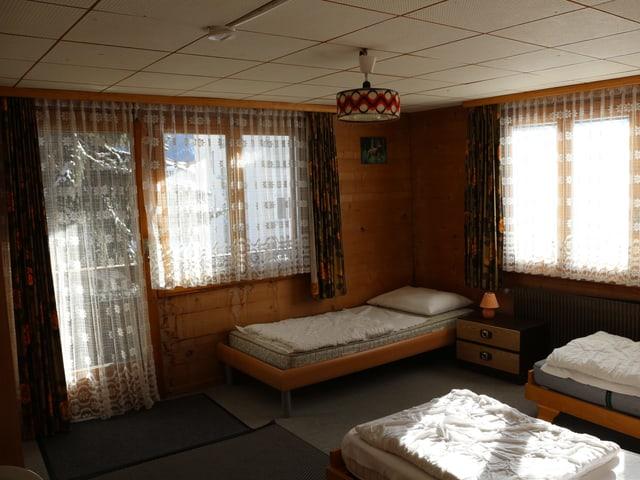 Zimmer mit mehreren Betten und Holzvertäfelung.
