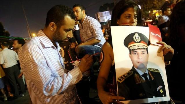 Protestierende halten ein Plakat von Abdel Fattah al-Sisi hoch.