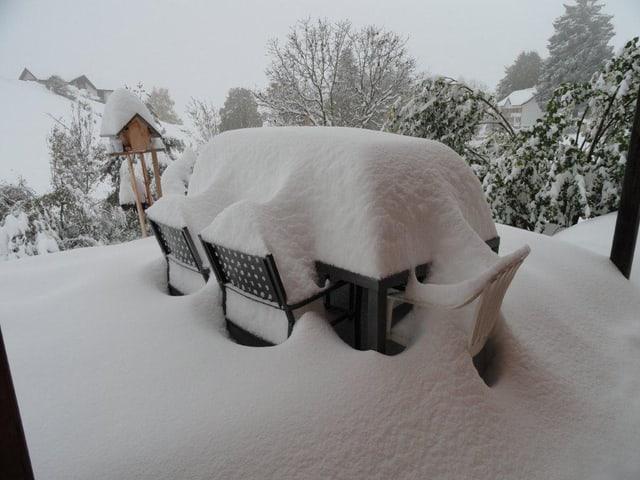 Gartentisch und Stülhe mit rund einem halben Meter Schnee bedeckt.