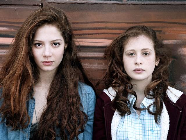 Zwei Mädchen stehen nebeneinander und schauen in die Kamera.