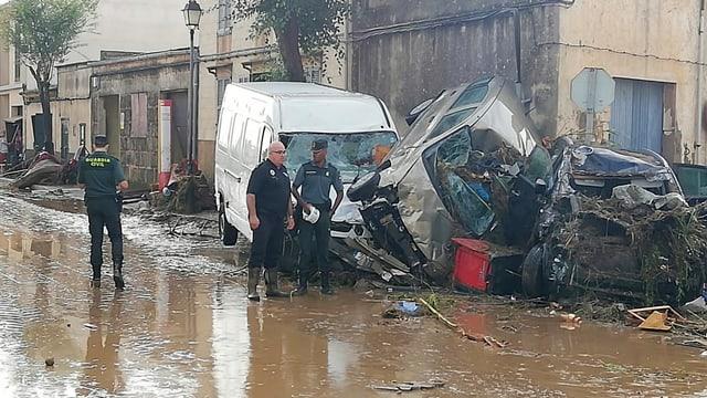 Polizisten schauen sich auf einer überfluteten Strasse kaputte Autos an.