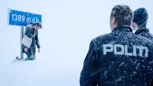 Zwei Polizisten im Schneegestöber betrachten einen toten Mann, der an eine Tafel gebunden wurde