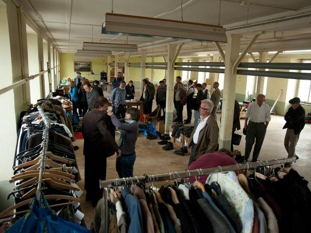Überblick über Fabrikhalle mit Ständern voll Kleidung, Schuhen, Hüten
