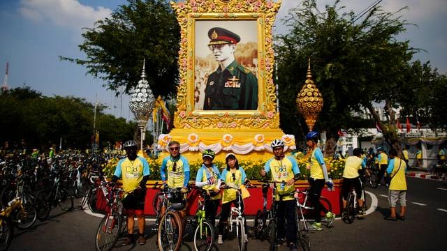 Radfahrer vor einem Bildnis des Königs