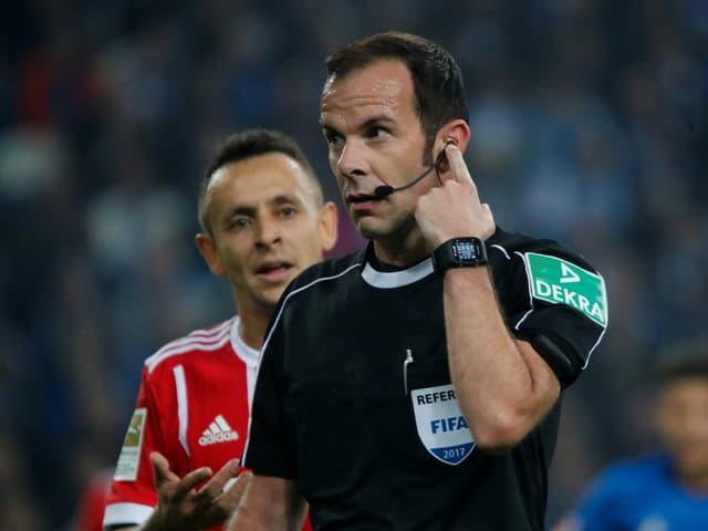 Marco Fritz greift sich ans linke Ohr, um mit dem VAR Kontakt aufzunehmen.