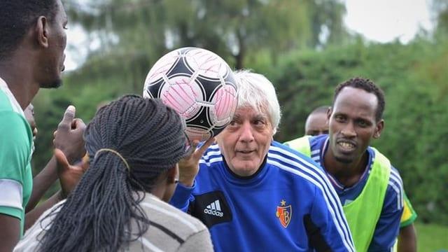Willy Schmid spielt mit Jugendlichen Fussball.
