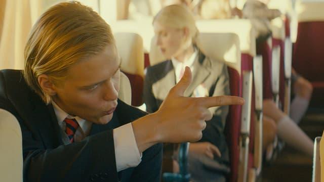 Junge mit blonden Haaren schiesst mit einem Finger in einem Schulsbus sitzend.