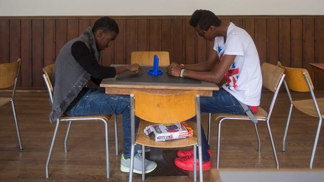 Zwei Männer spielen an einem Tisch das Spiel Vier gewinnt.