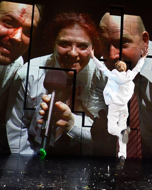 Bühnenbild: Ein Mann im weissen Anzug springt in die Luft. Auf einer Videoprojektion im Hintergrunf sind drei Menschen zu sehen, der eine mit blutiger Stirn.