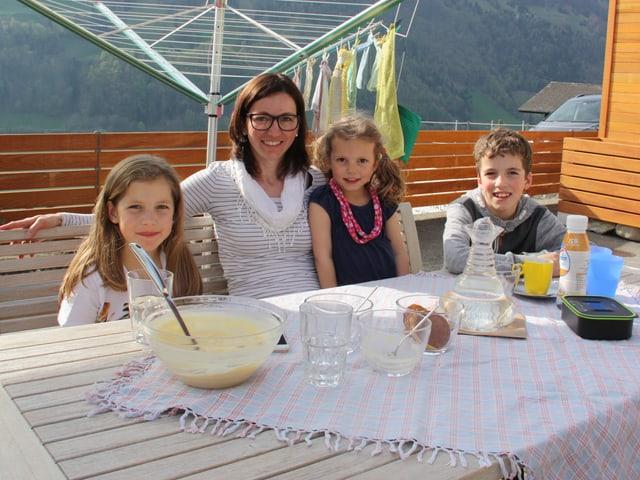 Eine Mutter sitzt mit ihren drei Kindern auf einer Terasse vor einem gedeckten Tisch.