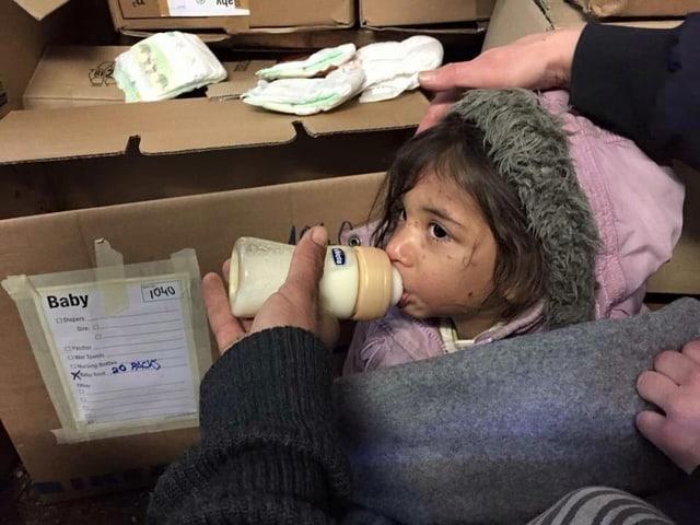Kleines Mädchen trinkt aus einem Milchfläschen