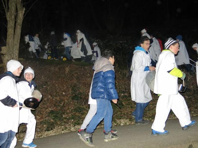 Weiss gewandete Fasnächtler gehen einen Waldweg hoch.