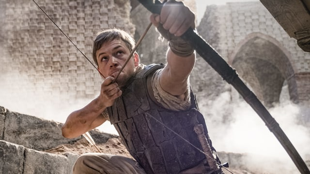 In the picture, Taron Egerton can be seen as stretching a bow with arrows.
