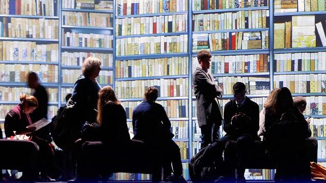 Besucher stehen und sitzen vor einer grossen Bücherwand.