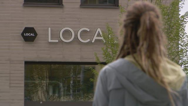 Eine Frau vor dem Local Logo