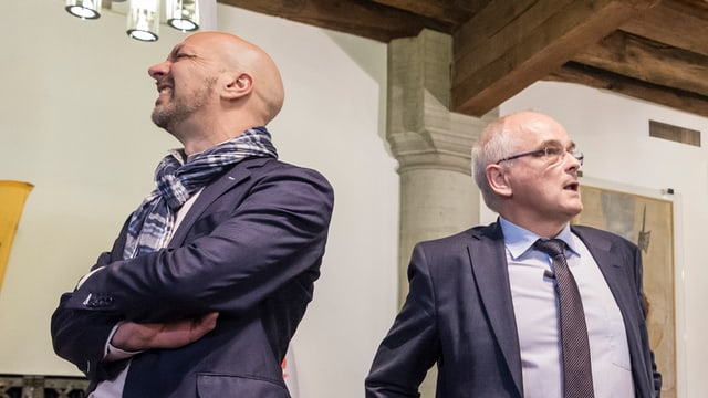 Zwei Männer stehen mit dem Rücken gegeneinander.