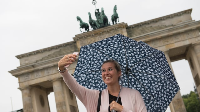 Frau mit Regenschirm macht ein Selfie vor der Siegessäule in Berlin.