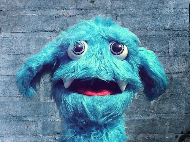 Eine blaue, zottelige Puppe mit grossen Augen.