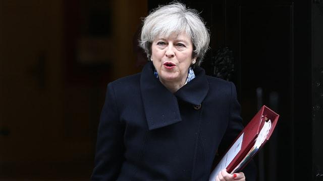 Theresa May mit einem Ordner in der Hand vor schwarzem Hintergrund.
