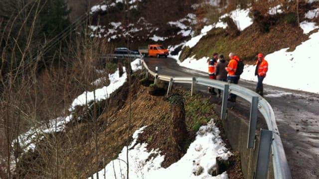 Gemeindearbeiter begutachten die Wiesenbergstrasse nach dem Erdrutsch.