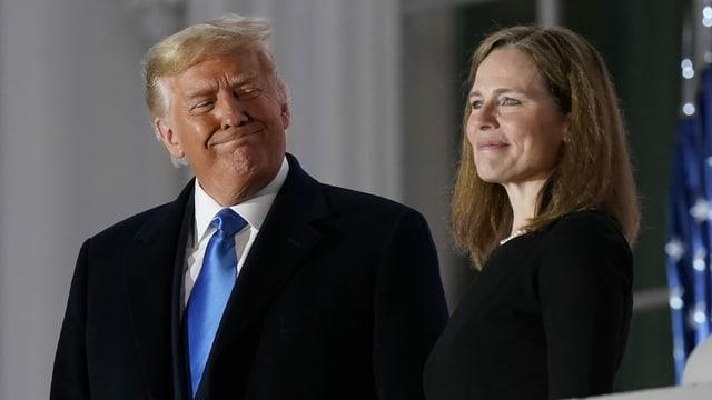 Donald Trump lächelt Richterin Amy Coney Barrett an.