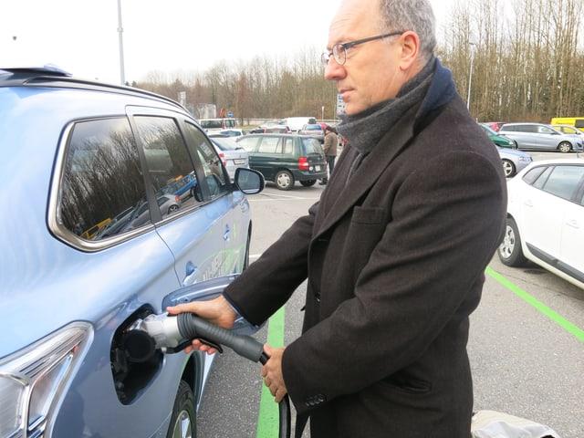 Urban Achermann, der Marketing-Direktor von Groupe E, lädt ein Hybridauto mit Strom auf.