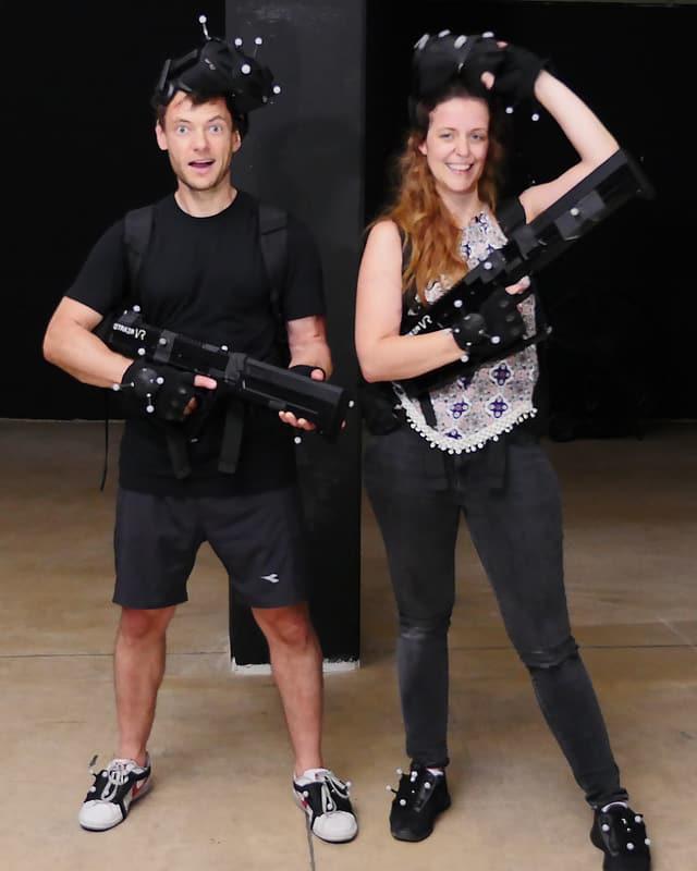 Jürg und Martina sind noch ziemlich benommen vom Spielen, posieren aber wie Helden für die Kamera in ihrer VR-Ausrüstung.