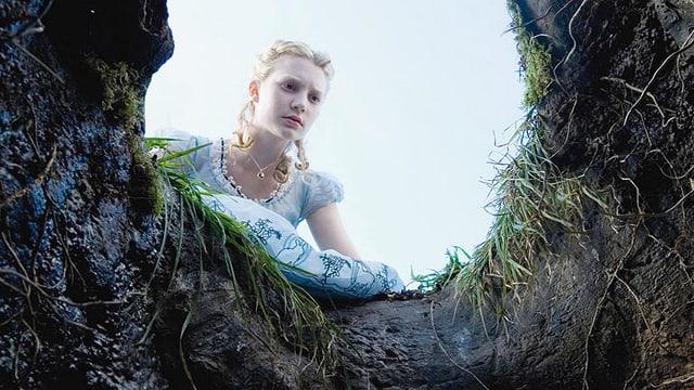 Ein blondes Mädchen blickt neugierig in ein Erdloch.