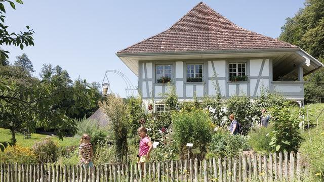 Zwei Kinder in einem Garten vor einem traditionellen Haus.