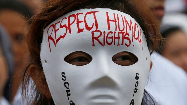 Eine Frau trägt eine Maske mit der Aufschrift Respect Human Rights.